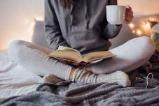 deco-cocooning-idée-de-linge-de-lit-blanc-et-gris-femme-qui-lit-une-tassé-de-café-guirlande-lumineuse-sur-le-fond